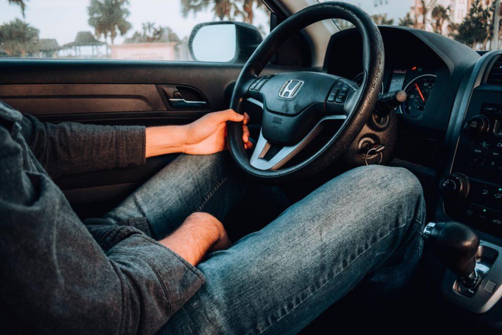 Man sitter i en bil och håller händerna på ratten.